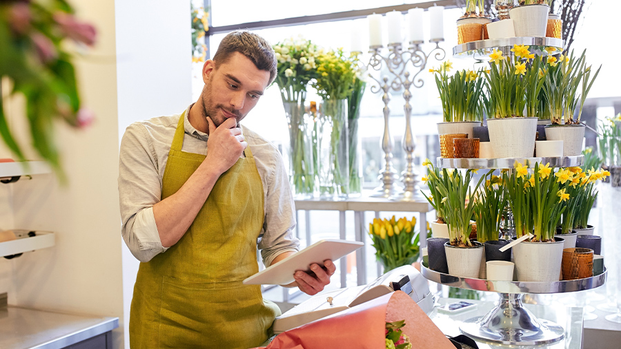 Florist Reviewing Information on His Tablet