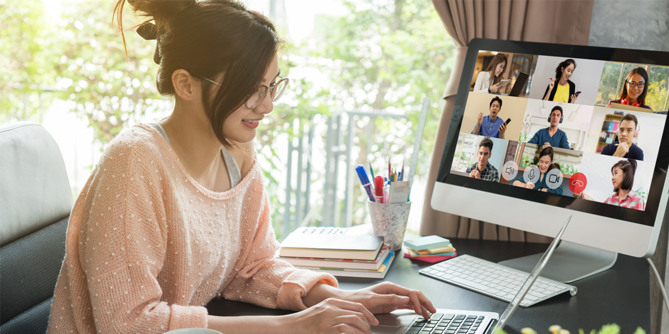 A young female professional video conferencing with her team while working remotely