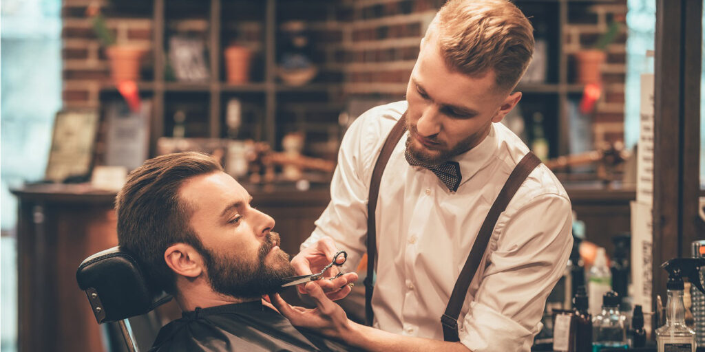 Barber trimming a customer's beard with scissors