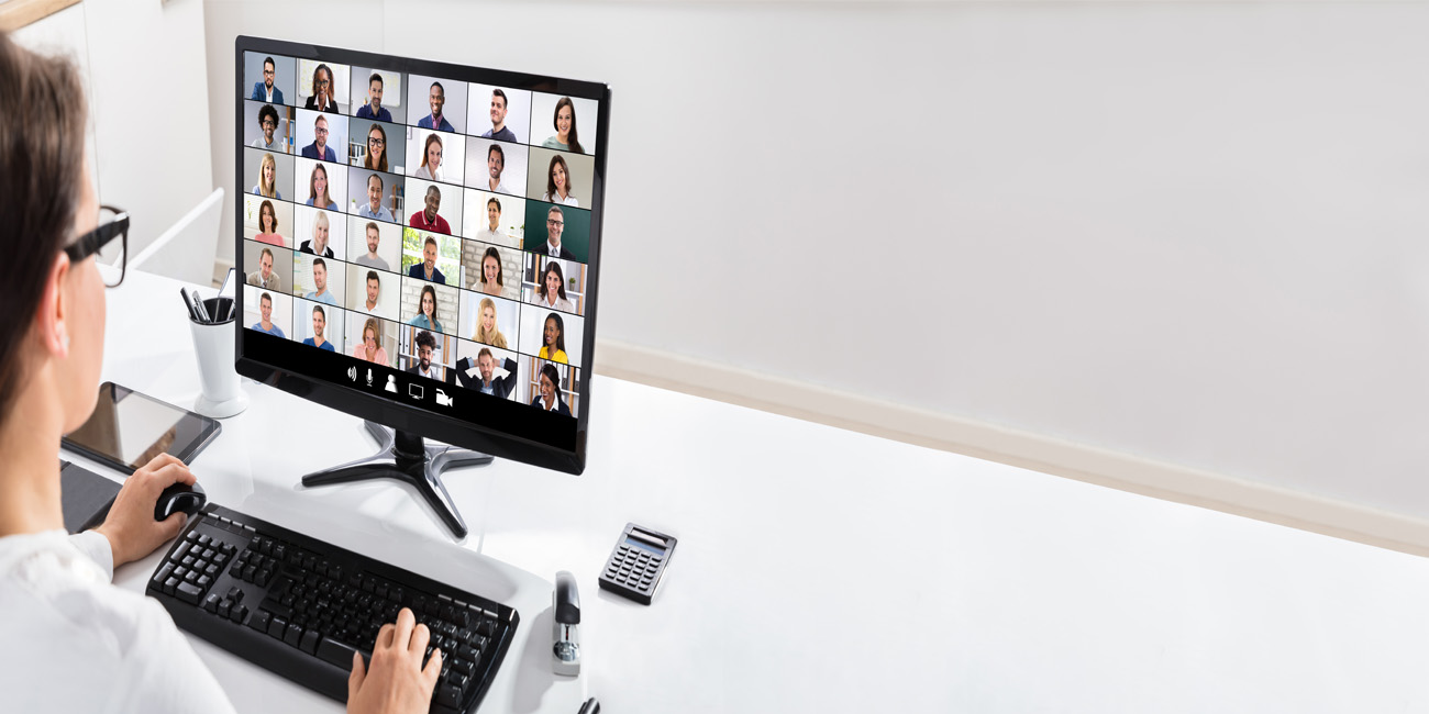 Woman using computer to joining a large online video conference call