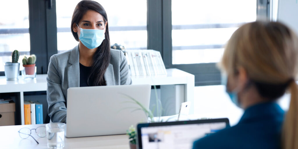 Two businesswomen wearing masks as the share a co-working station