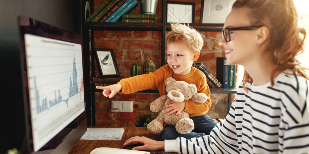 Young mother working from home as her son ask about data analysis on her computer screen