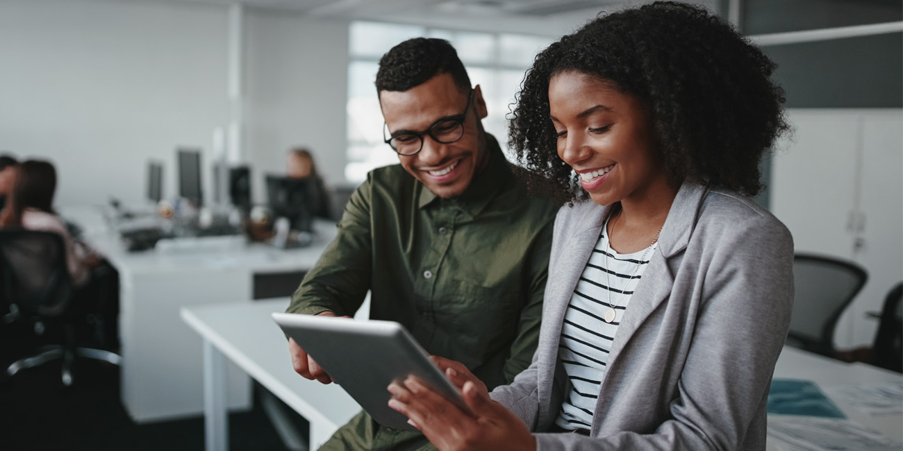 Young African American female and male coworker review tech trends