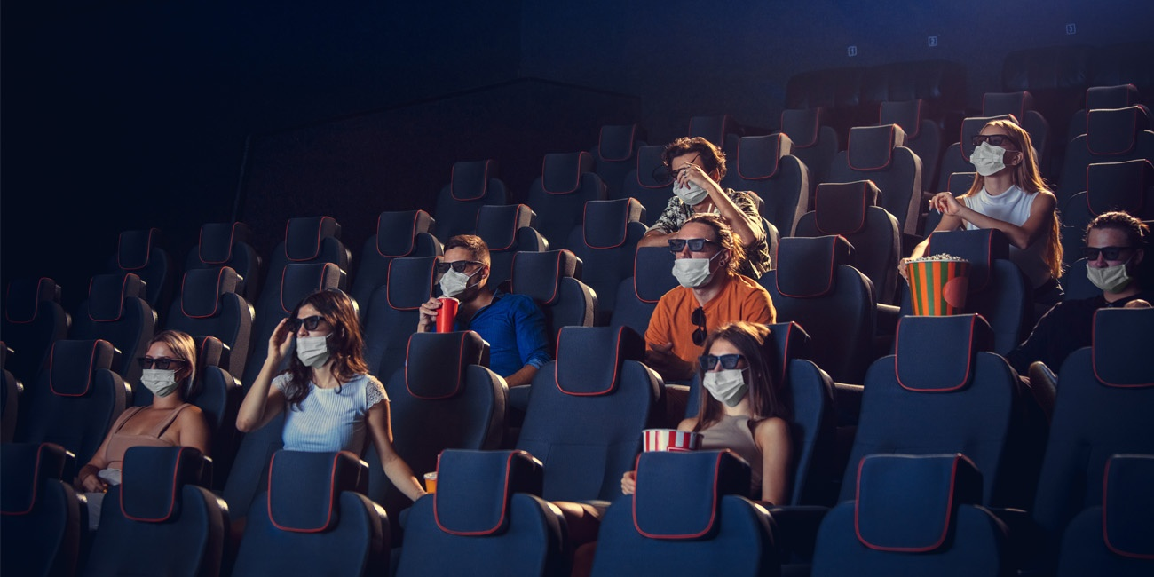 Diverse group of people watch 3D movie physically distanced and wearing face masks