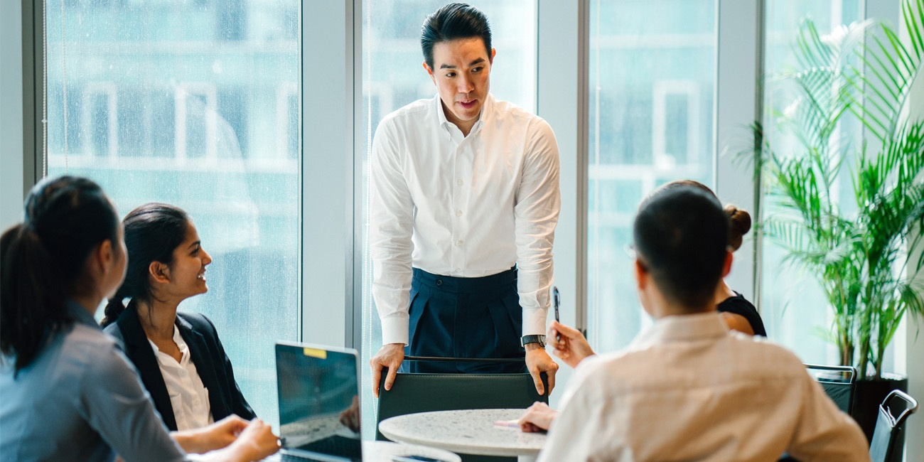 Asian male leader motivates team of diverse coworkers