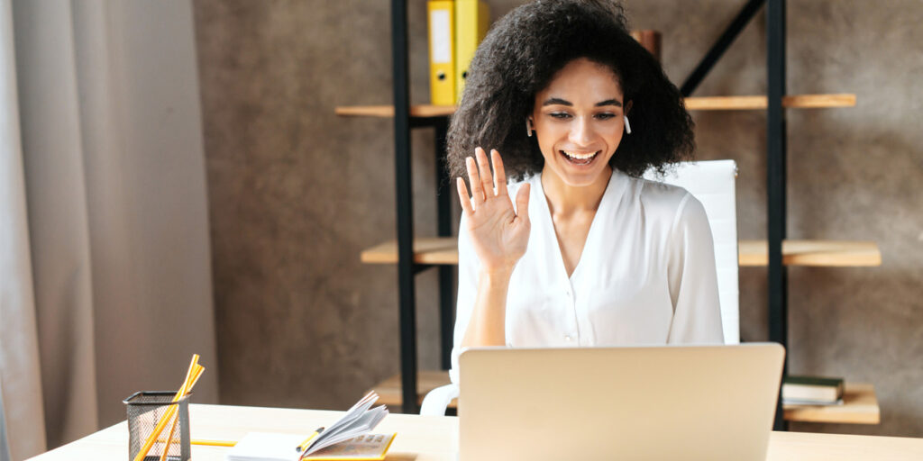 Young female employee introducing self during video call on laptop