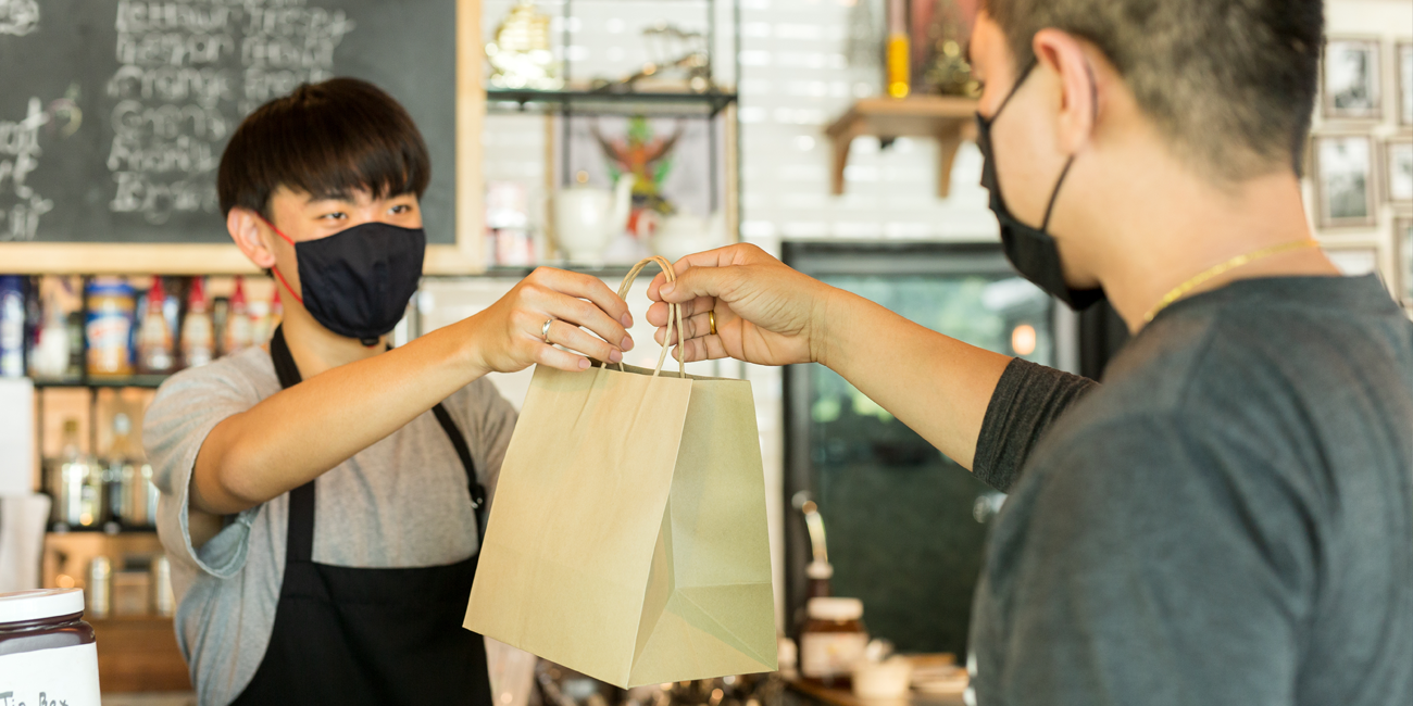 small business owner with face mask is handing a customer their purchase