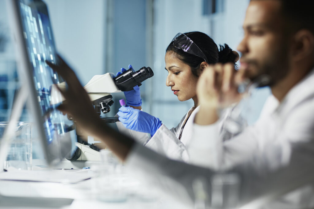 Woman working in a modern lab facility with a microscope and specimen.