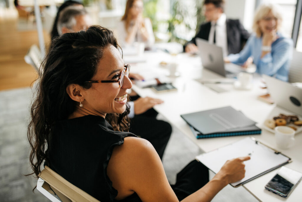 Hispanic Woman at Conference Table Laughing